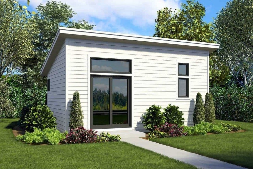 This is a small farmhouse-style home with bright white shiplap exterior walls paired with modern glass windows and doors with a concrete walkway through the grass lawn.