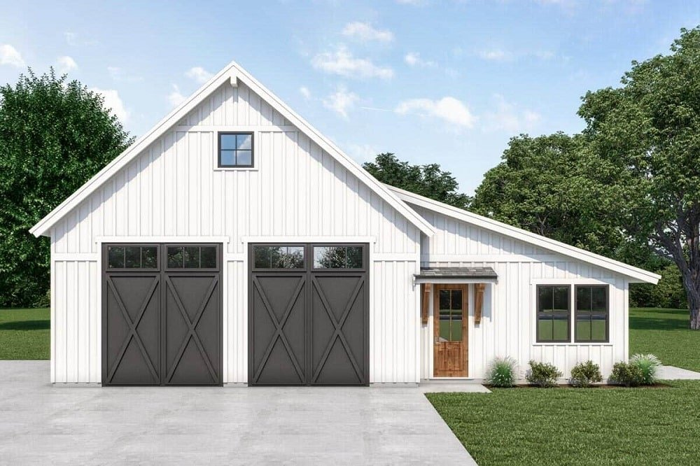 The farmhouse-style home is dominated by its large barn-style garage doors with a dark tone to contrast the white exterior walls. Beside this is the main door with a wooden tone.