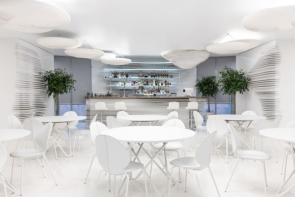 This is a bar with a consistent white tone to its tables, chairs and walls.