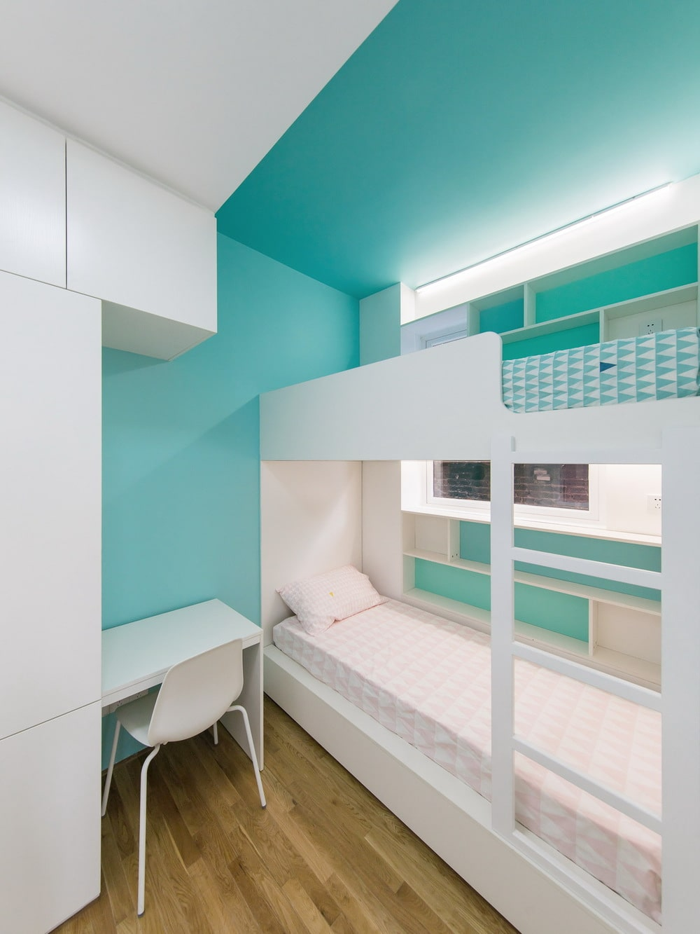 This is a children's bedroom with a white bunk bed and built-in study desk to the cabinet that contrasts the blue walls and ceiling.
