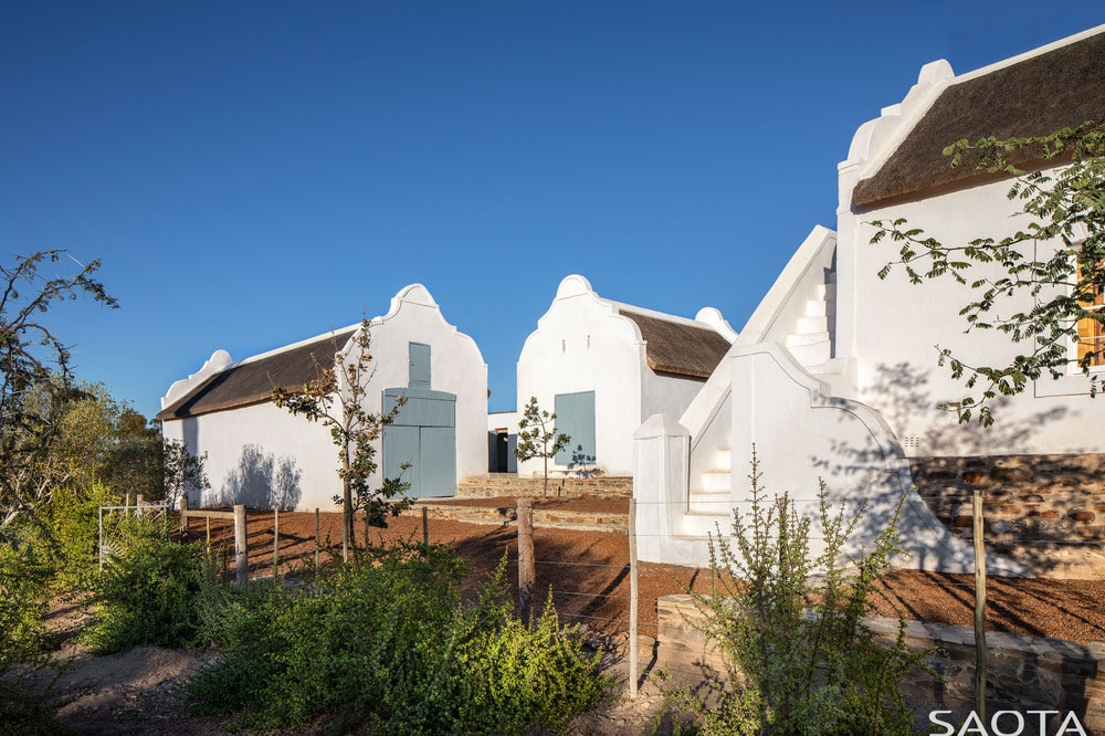 This is an exterior view of the property featuring the three white houses bordered with a simple fence.