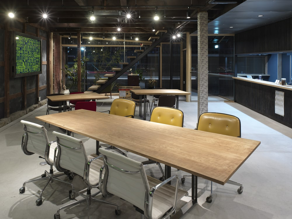 This is a large wooden rectangular conference table surrounded by office chairs and topped with modern lighting,