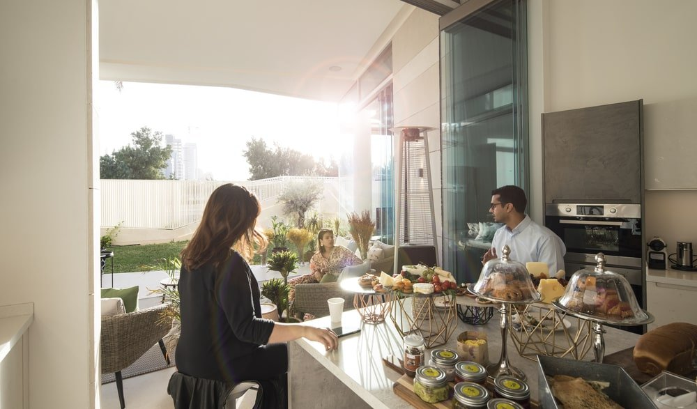 The kitchen has glass panels that open up to the covered patio outside making the kitchen bigger.