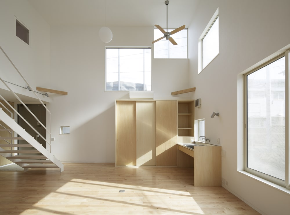 this is a view of the interior showcasing the main door, the staircase and a large wooden structure on the far corner with an attached sink.
