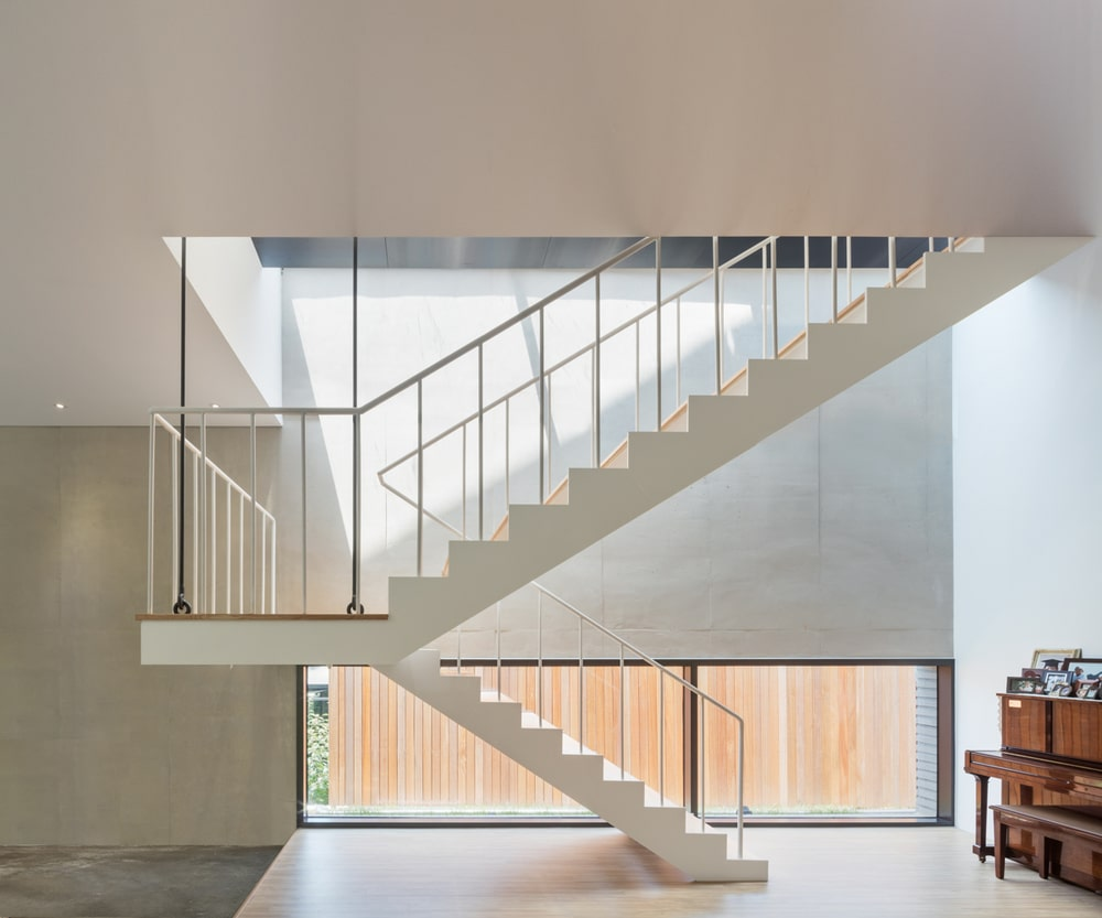 This is the white staircase with a modern design bathed in natural lighting.