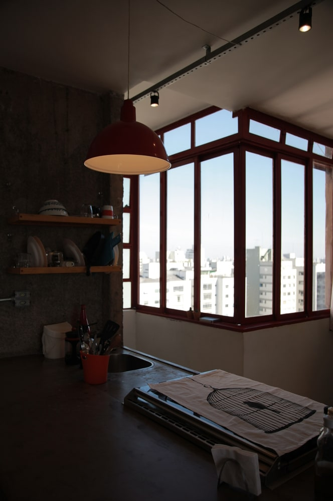 This window gives a city skyline view for the kitchen island that is topped with a dome pendant light.