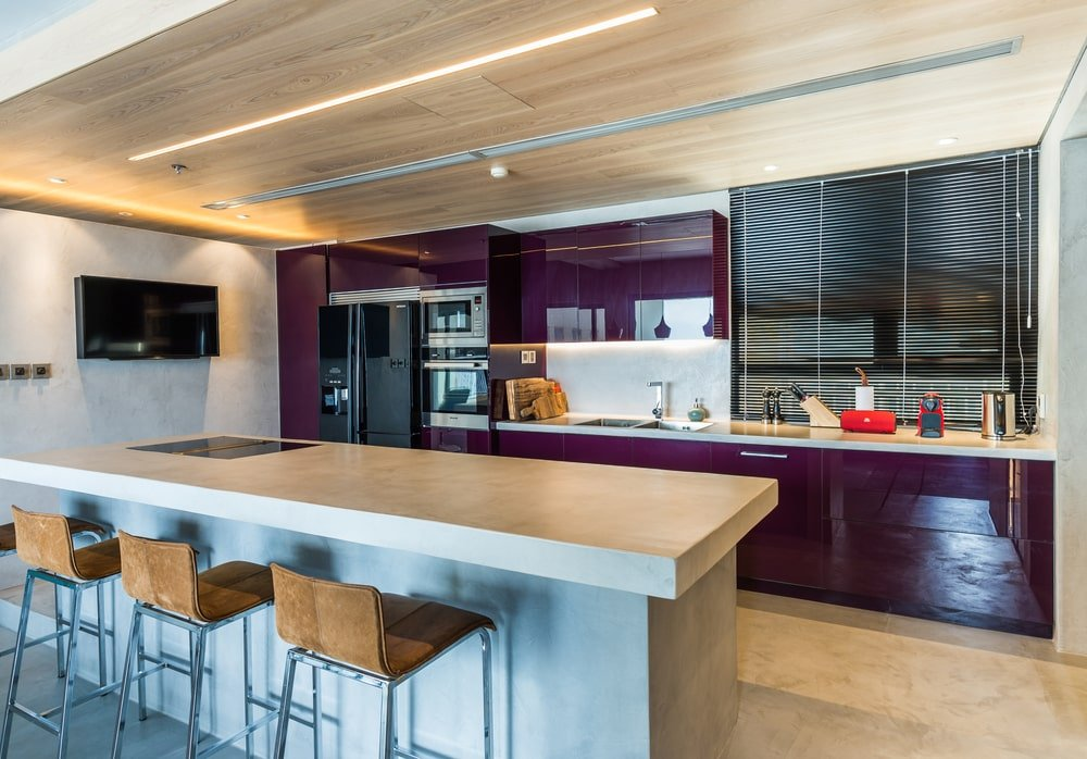 This purple wall matches well with the purple cabinetry of the kitchen across from the island.