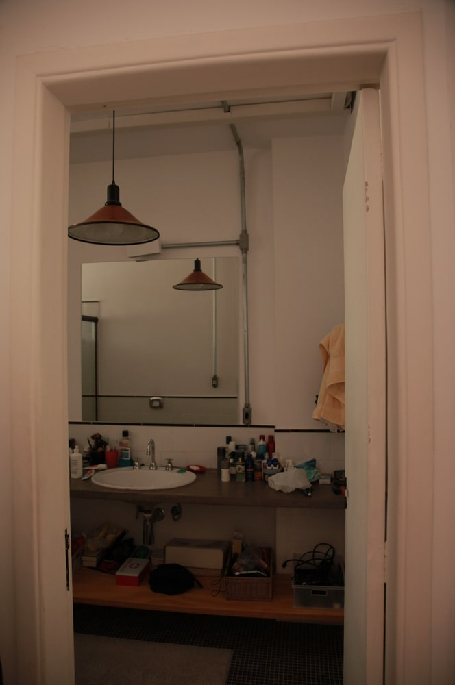 This is a look at the bathroom that has a rustic wooden support for the sink topped with a large wall-mounted mirror.