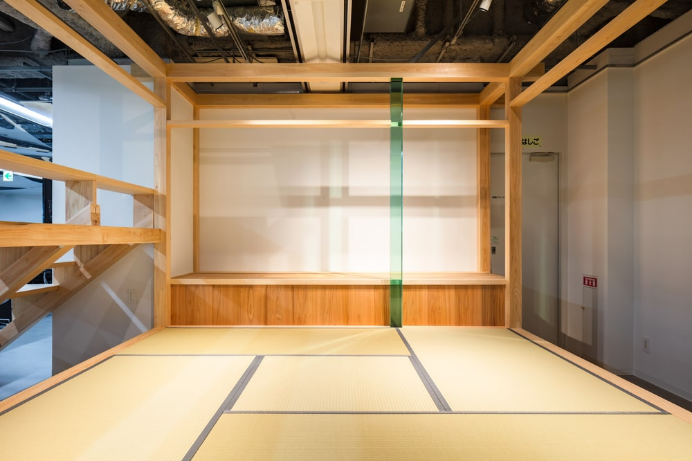 This is a room behind the wooden steps that has a traditional-style Japanese tatami floor.
