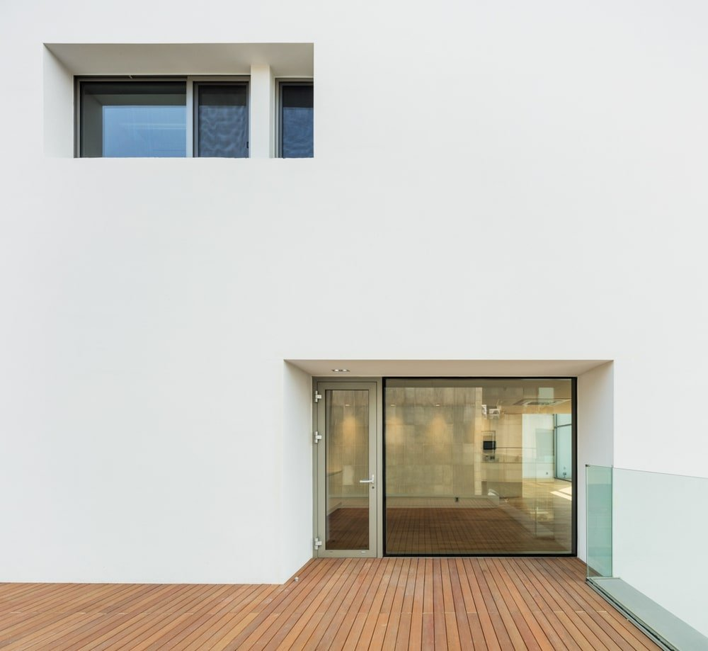 This is a close look at the balcony doors with glass structure and a large beige wall.