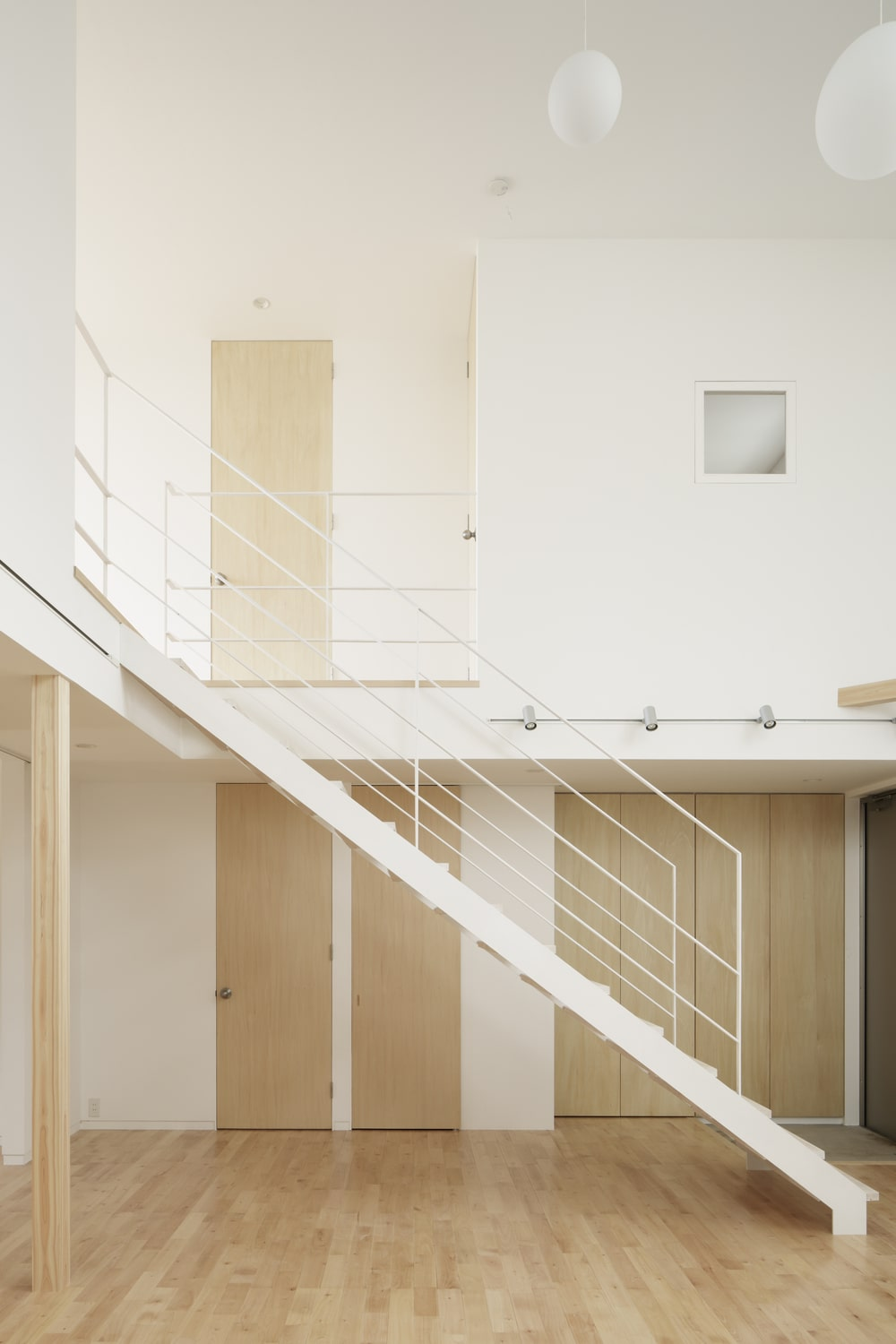 This is a closer look at the white modern staircase that pairs well with the light hardwood flooring.