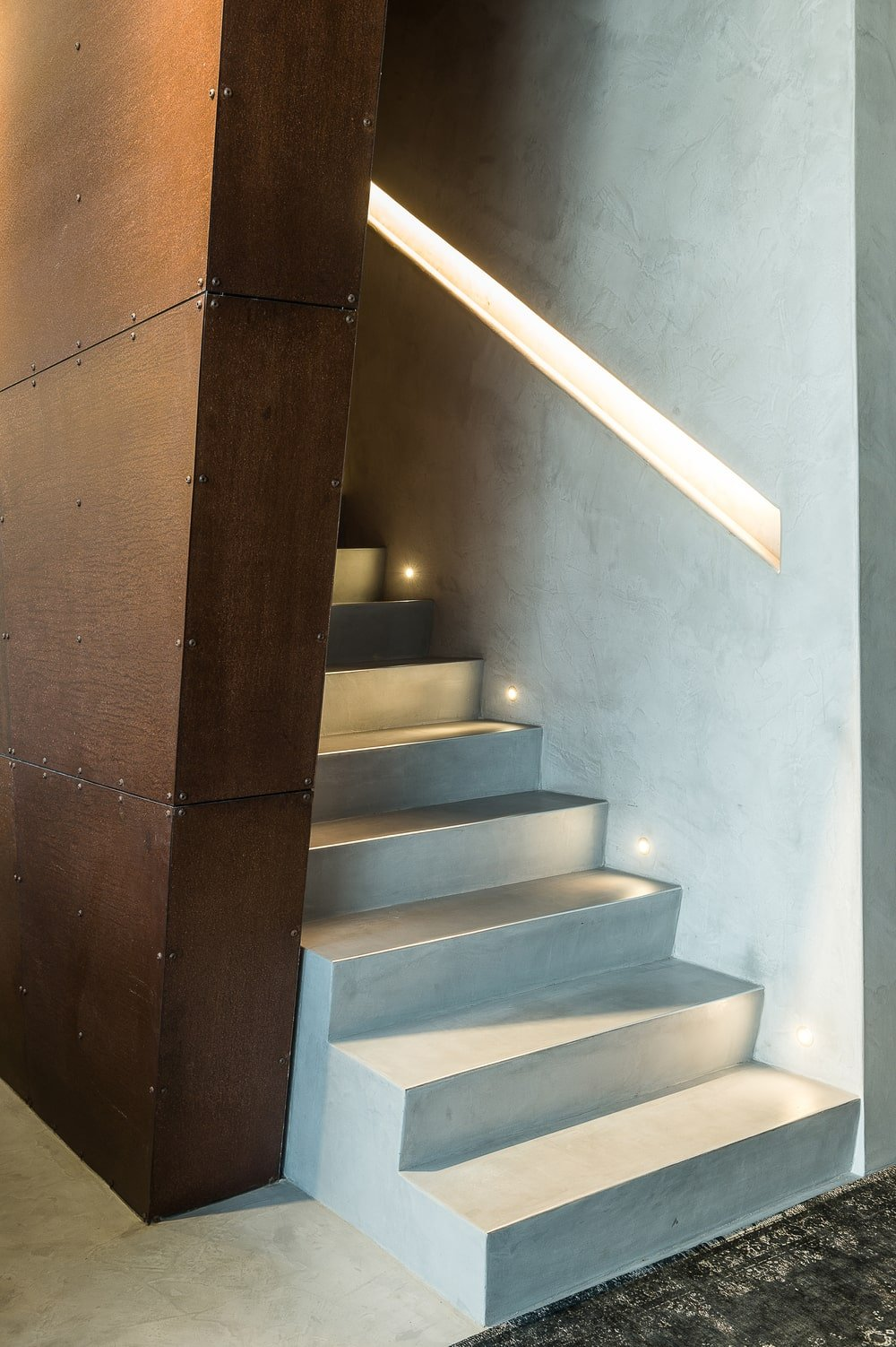 This is a close look at the staircase that has a wood paneled wall on the side and modern lighting on the other side.
