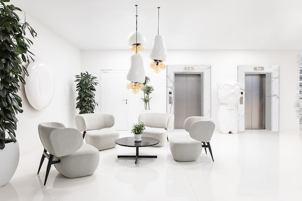 The area is adorned with multiple potted plants that bring color to the monotonous white walls and floor.