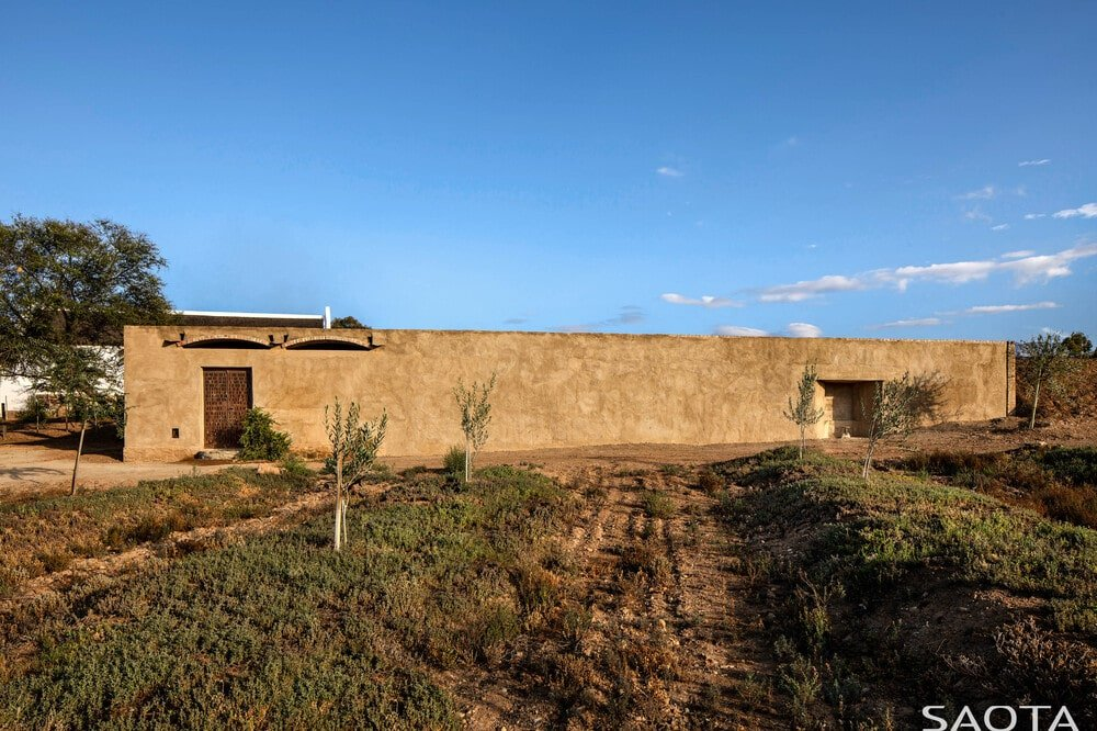 The structure has a simple and minimalist design that makes it a part of the surrounding landscape.