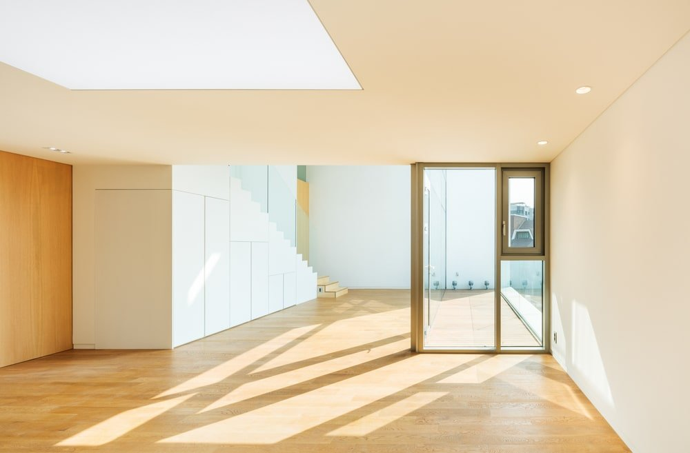 This is a spacious area with hardwood flooring, a glass divider and a skylight in the middle.