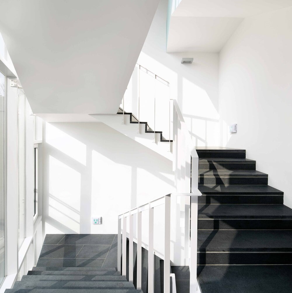 This is a close look at the stairs that has dark steps contrasted by the white walls and ceiling.