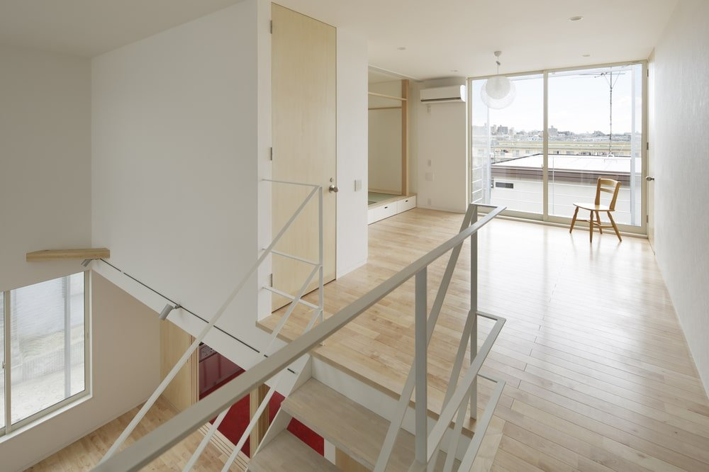 This is a look at the second-level landing with a light hardwood flooring and metal railings.