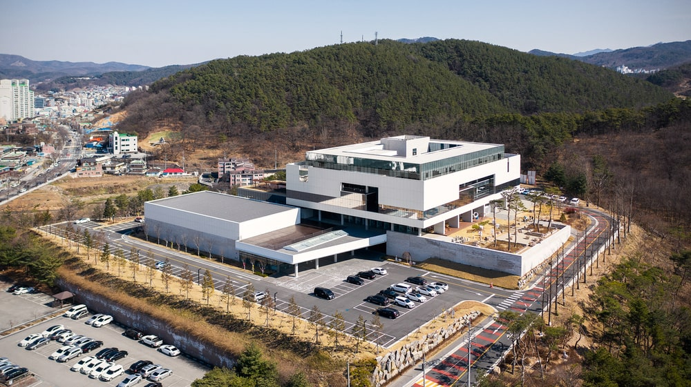 This aerial view of the building showcasing the surrounding area with a mountain terrain just behind the building.