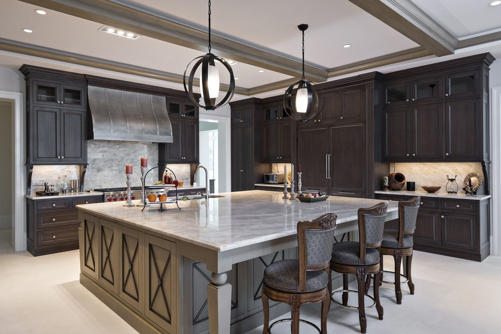 This is a close look at the kitchen that has a large kitchen island in the middle paired with wooden stools and surrounded by dark wooden cabinetry.