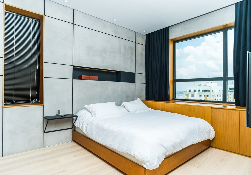 The primary bedroom has a large platform bed that is attached to the wooden cabinetry built into the wall under the window with dark curtains.