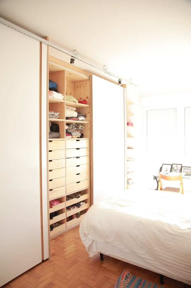 Across from the bed is a large wooden structure that has drawers and cabinets.