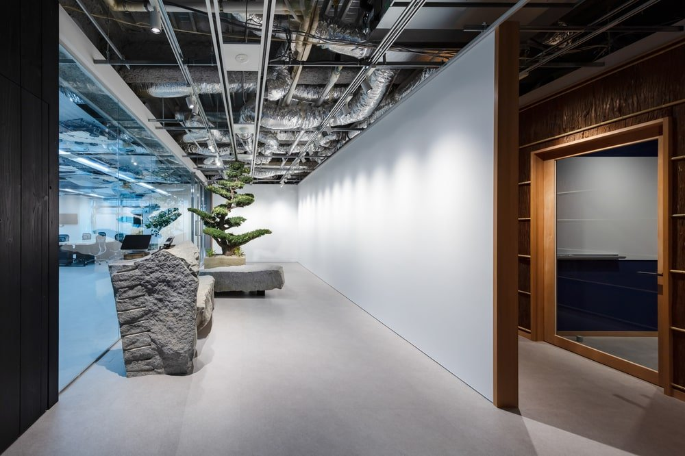 This is another hallway with a large glass wall adorned by a zen-like decoration of rocks and potted plants.