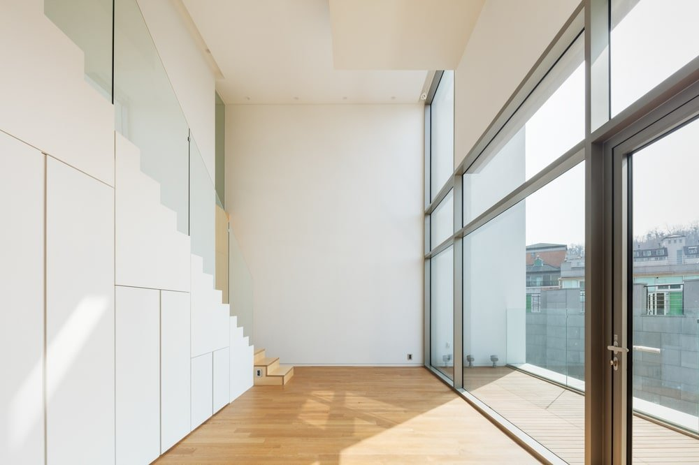 This is a large open area bathed in natural lighting that is coming in from the large glass wal across from the staircase.