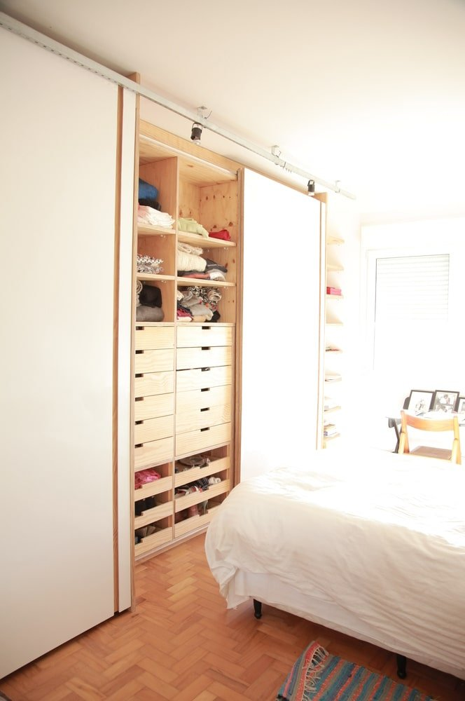 The bedroom also has a herringbone wooden flooring and a small study area on the side of the bed.