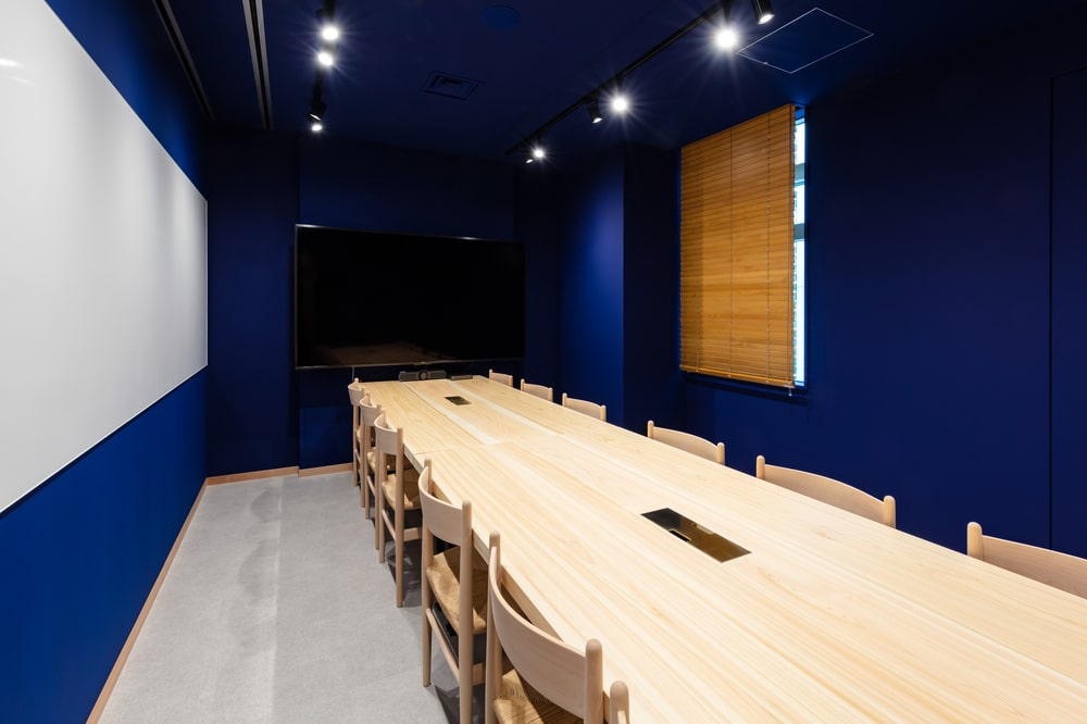 This is a large conference room with blue walls and ceiling making the light wooden table and chairs stand out.