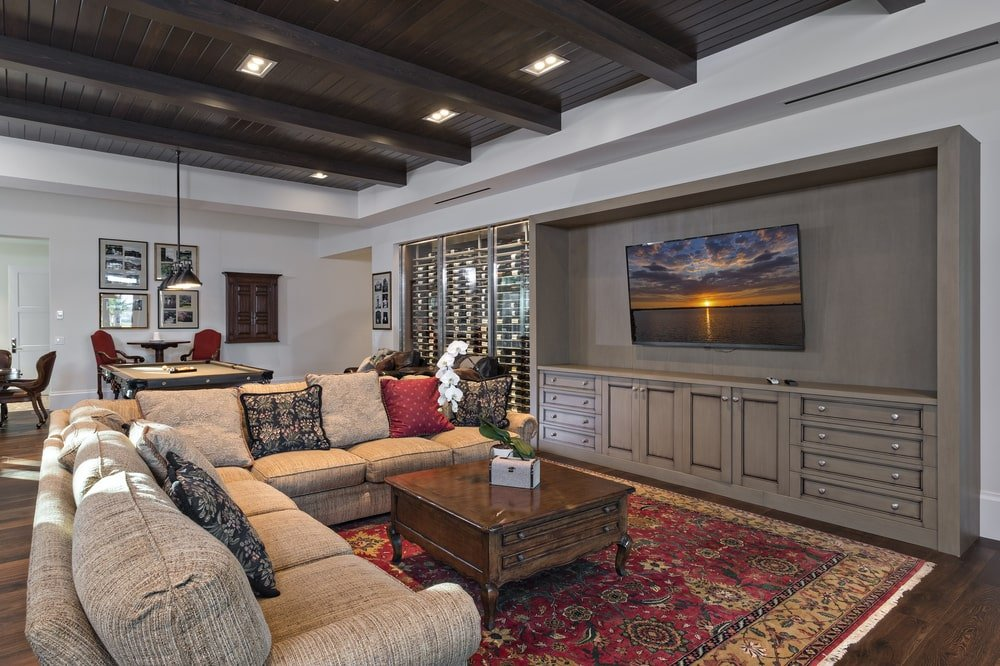 The family room has a large L-shaped sectional sofa and wooden coffee table across from the wall-mounted TV.