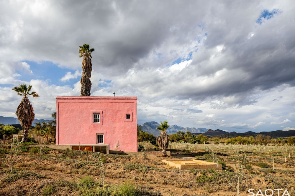 This is the back of the house showcasing a simple landscaping that makes the pink exteriors of the house stand out.