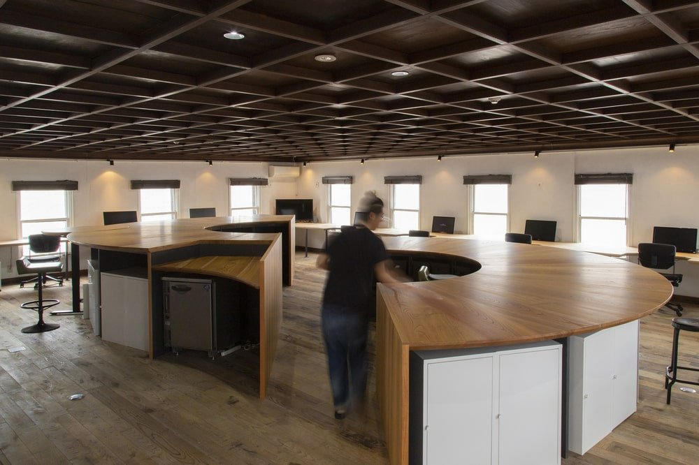 This is a look at the office area that has large wooden structures used as multi-function cubicles.