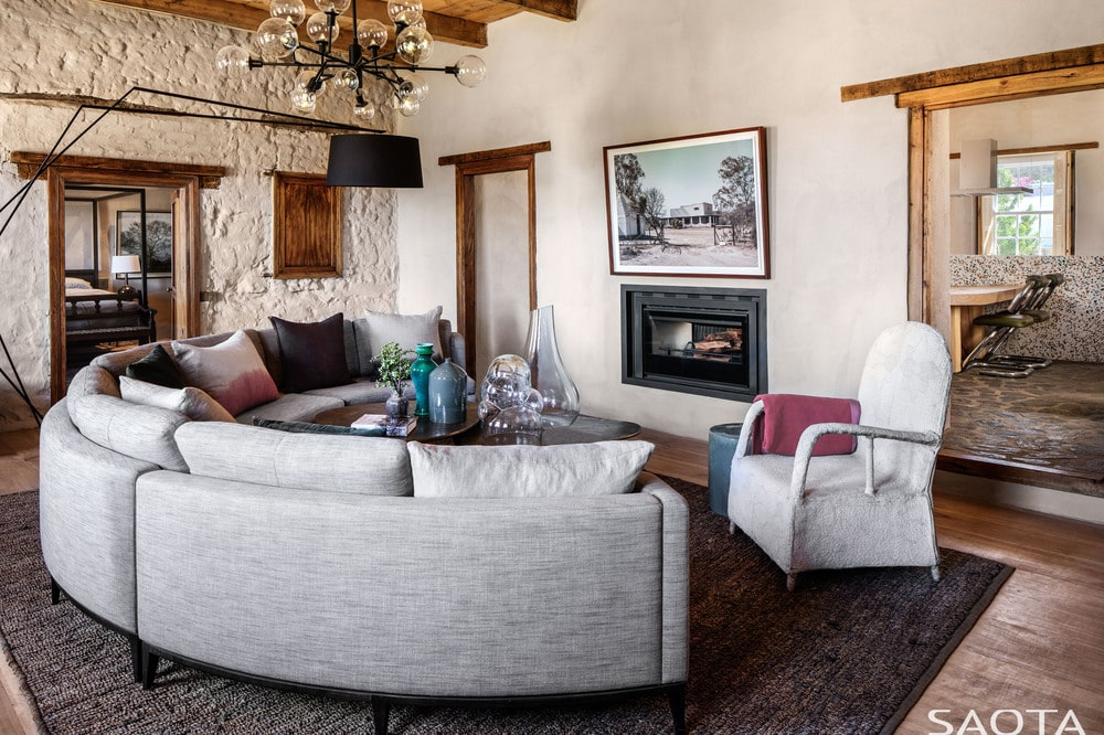 This is a living room with a large curved sectional sofa across from the modern fireplace topped with a wall artwork.
