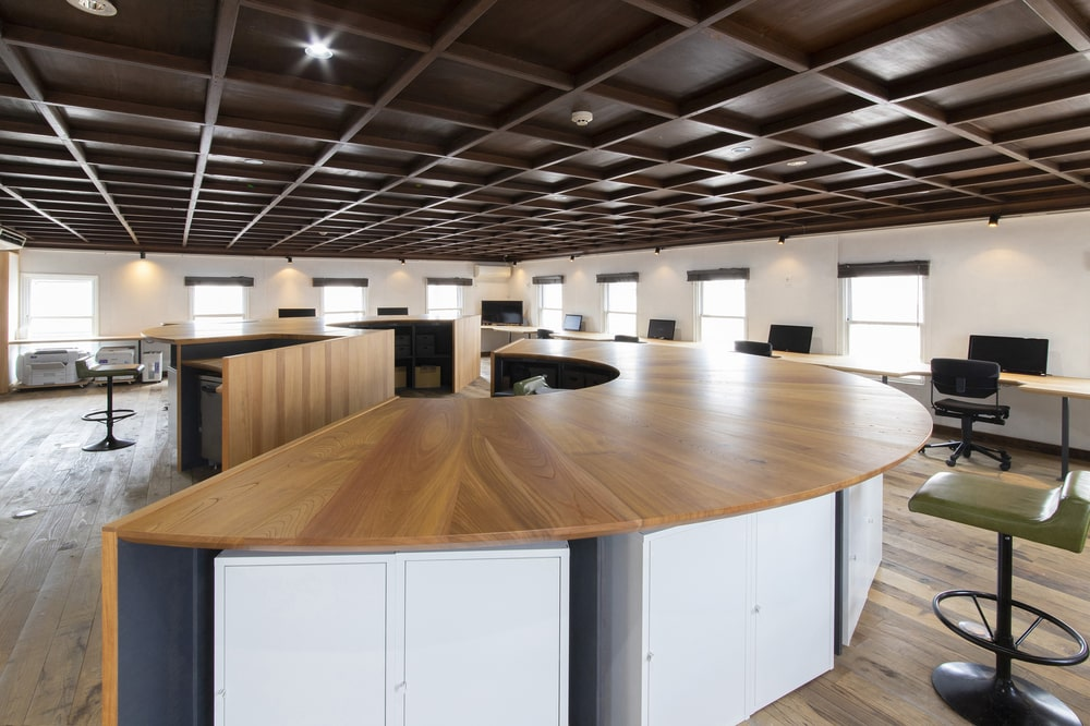 The large office area is topped with a coffered ceiling that has wooden exposed beams and recessed lights.