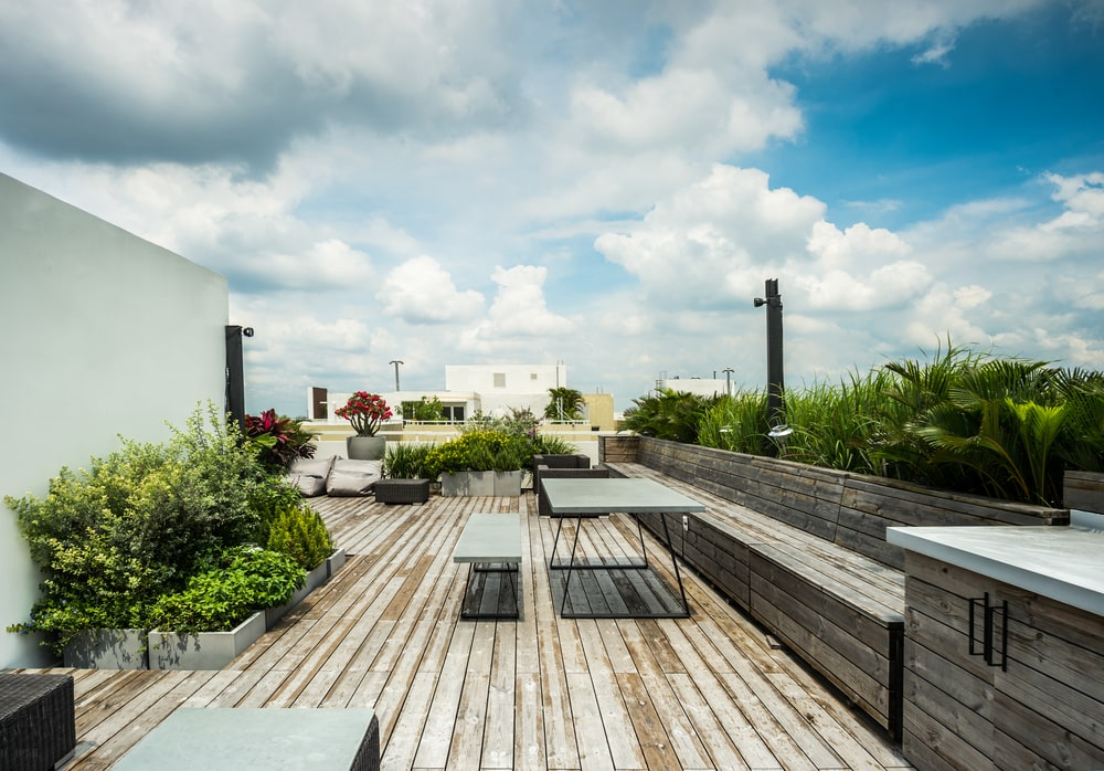 This is the rooftop patio with wooden flooring and built-in benches adorned by the various plants and shrubbery.