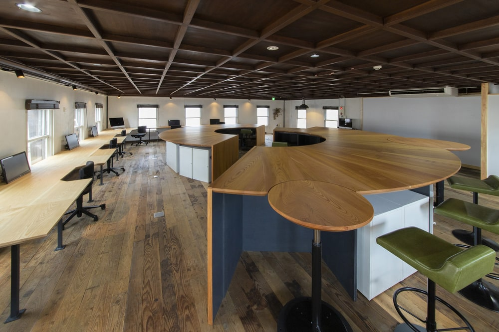 Along the wall near the large wooden structure is the long row of tables that are also used as offices.