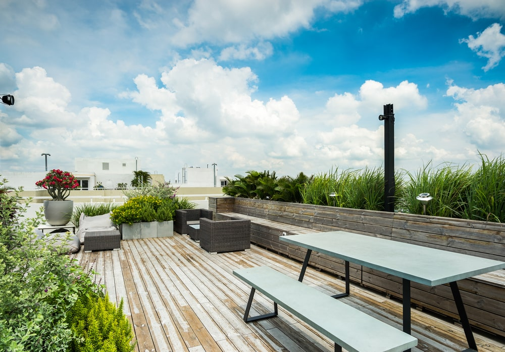 The large area is also fitted with an outdoor dining set adorned witha row of planters behind the built-in bench.