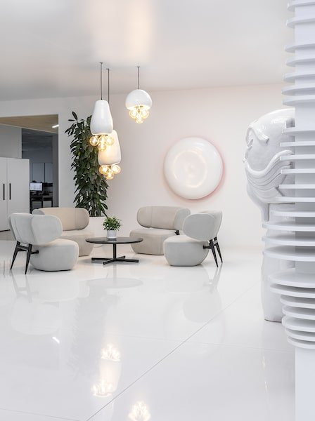 The white modern floor of the area is also reflective to scatter the warm lighting hanging above the coffee table.