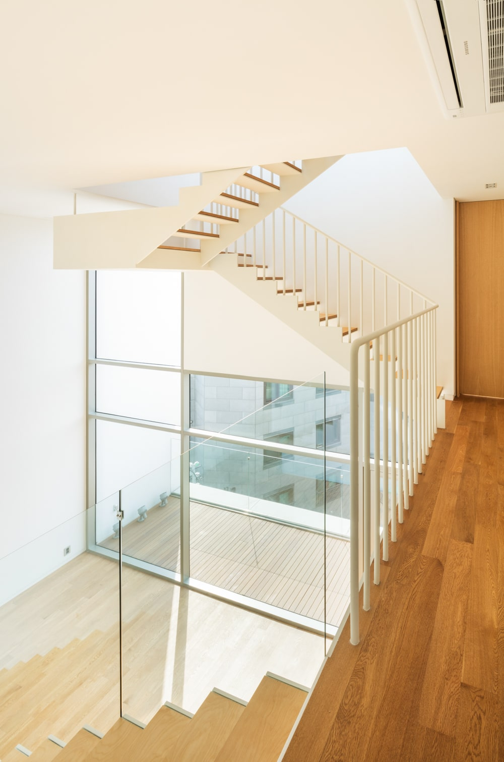 The staircase has a clear view of the floor below due to the glass walls.