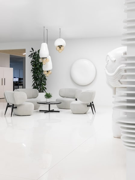 This view of the separate area showcases the contrast that the potted plants bring against the white monotones.