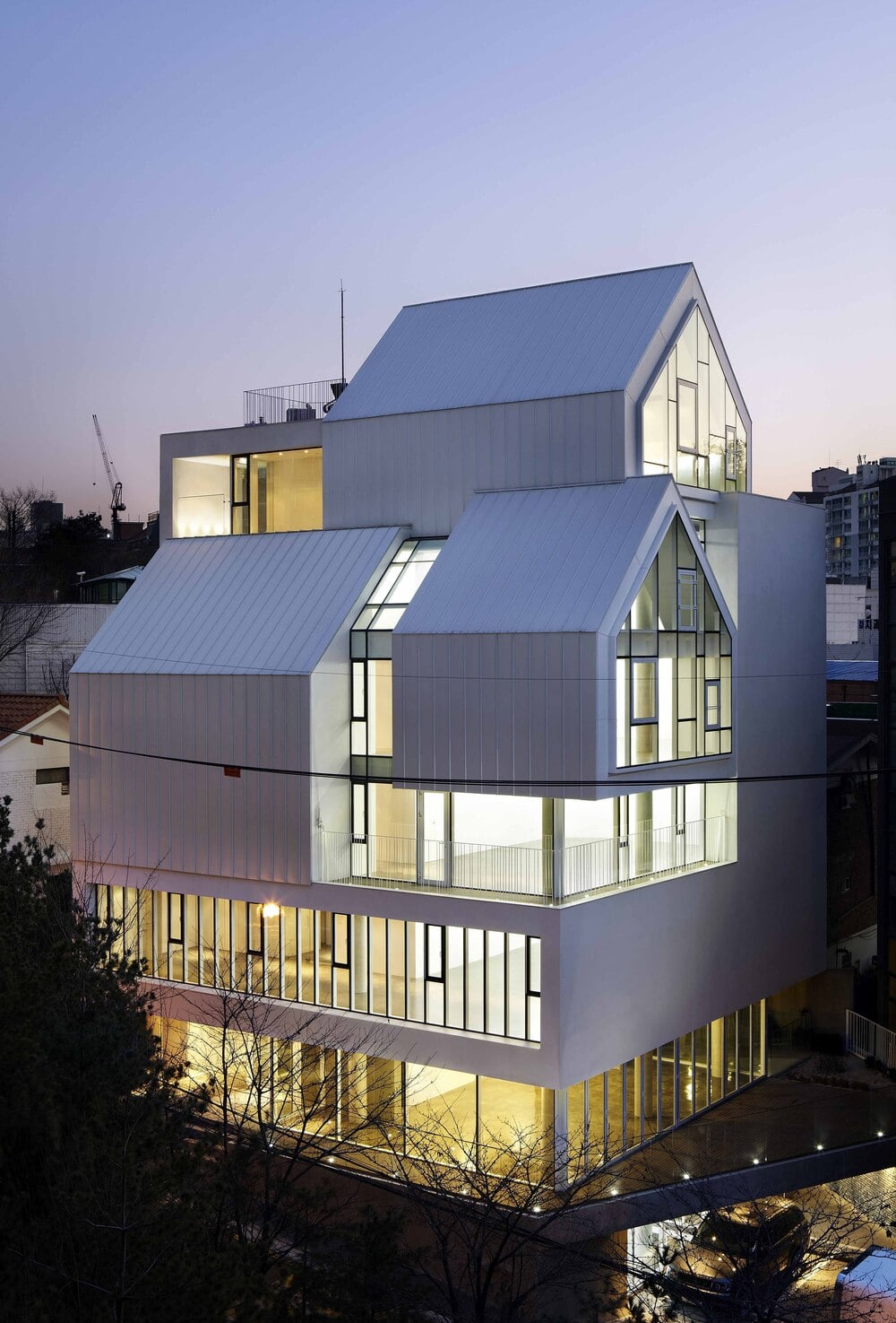 This is a nighttime view of the house that has bright white exteriors and warm yellow glow to its windows.