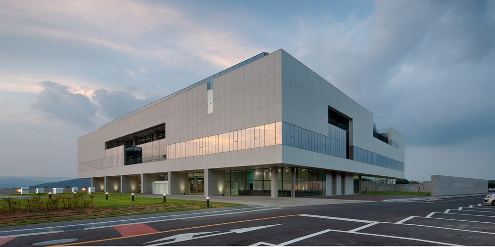 This is a full view of the building that has a modern design adorned by the large glass walls and pillars.
