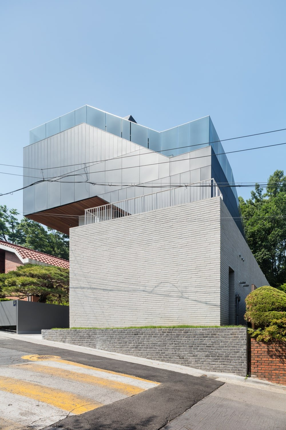 This is a street view of the house that has brick exterior walls and glass railing at the top.