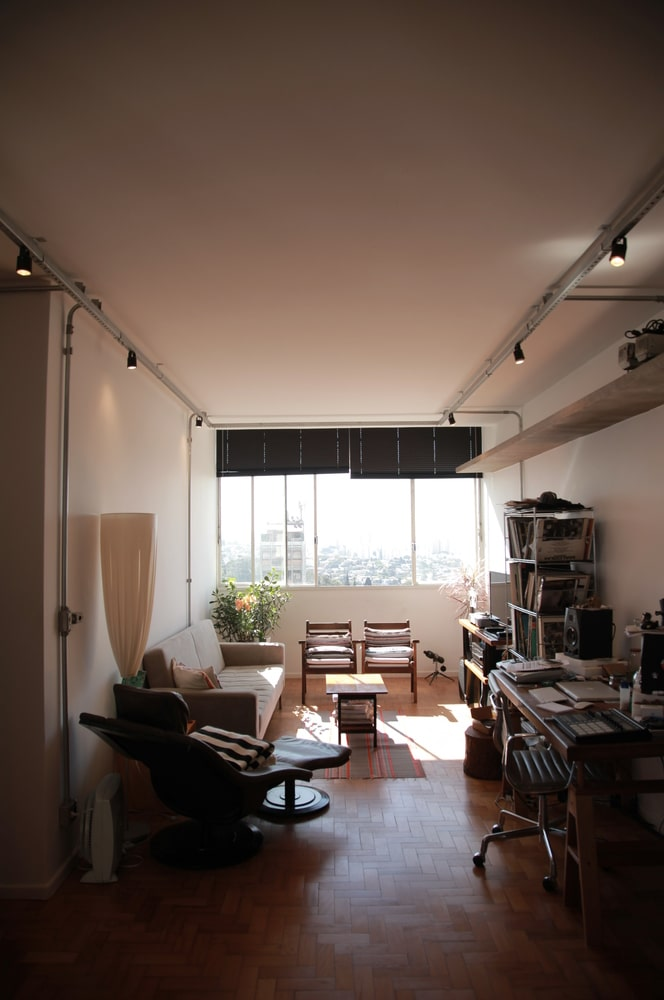 This is a close look at the apartment's living room area and office brightened by the large window on the far side.