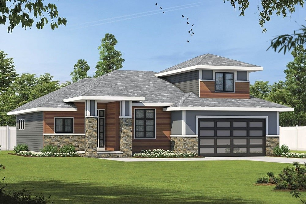 This is a front view of the house with stone sidings that go well with the large grass lawn of the landscape that also has tall trees and fences.