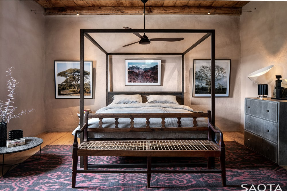 This is another look at the primary bedroom with its four-poster bed and bench at the foot of the bed.