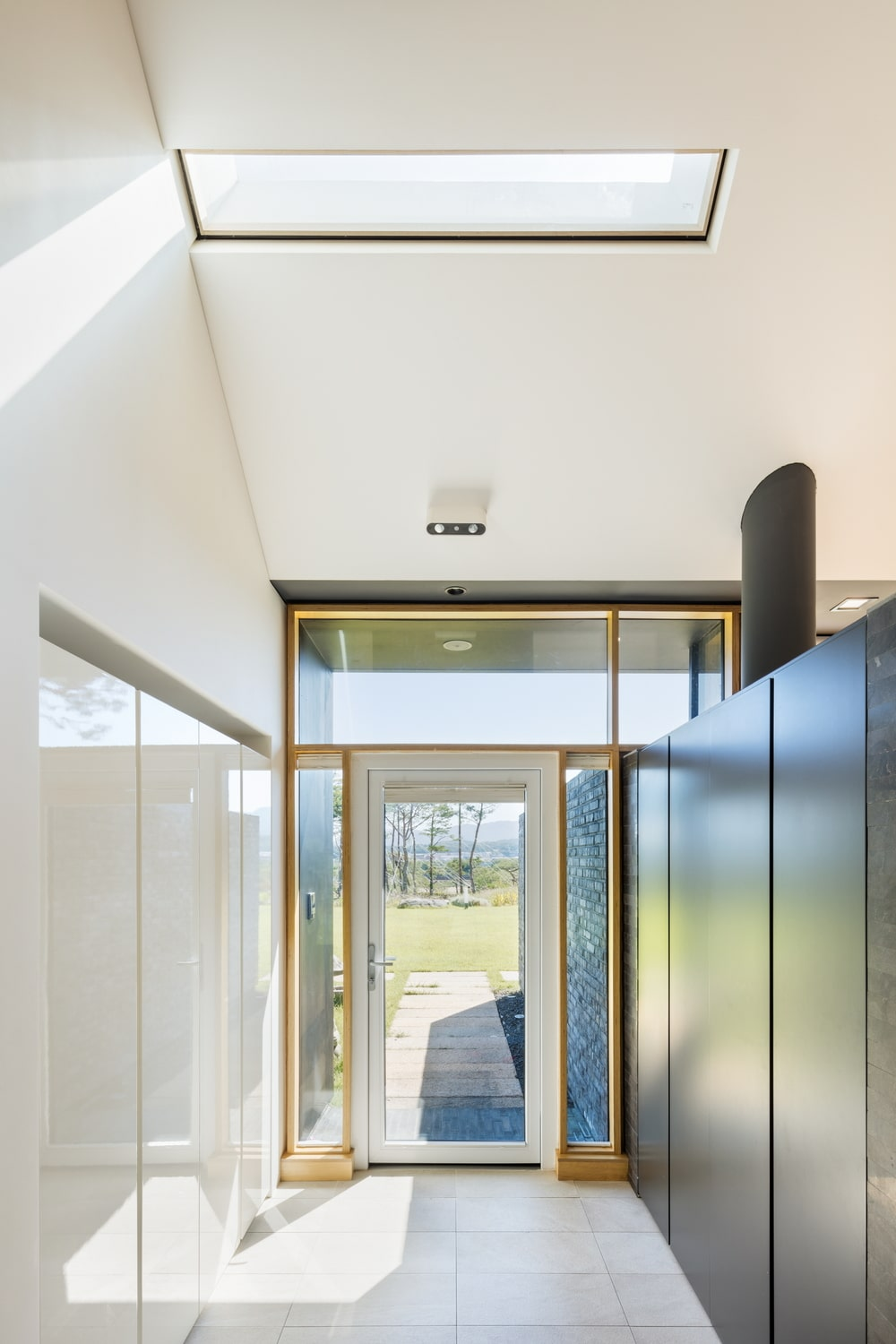 Upon entry of the house, you are welcomed by this simple foyer that has bright walls and arched ceiling brightened by the natural lights of the glass door.