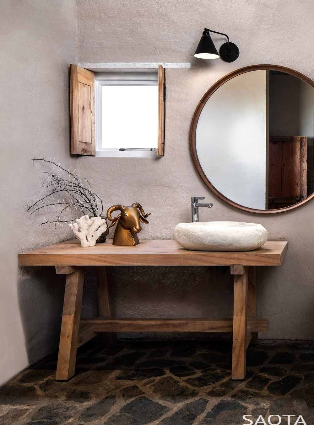 This is a close look at the rustic bathroom with a wooden table for the vanity to support the sink paired with a small window and a large mirror.