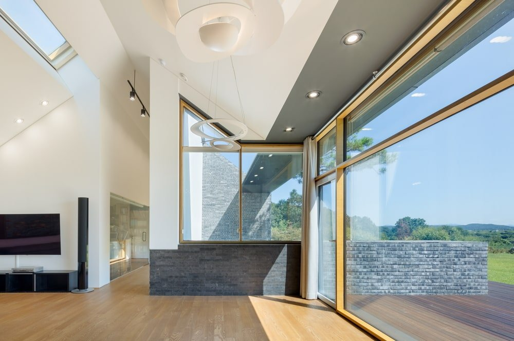 This is a view of the edge of the living room with a alrge open area hallway that leads to the glass door of the patio.