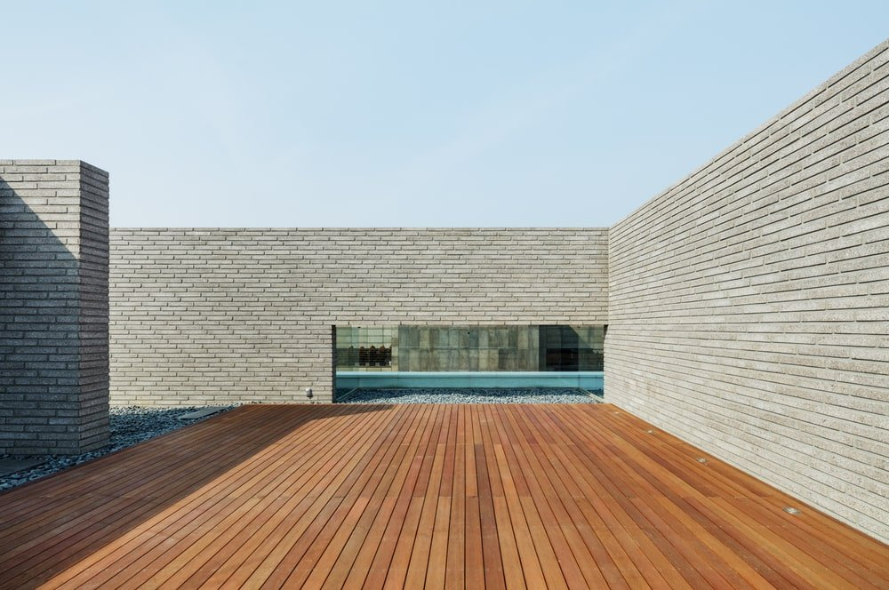 The rooftop terrace of the house has wooden deck flooring.